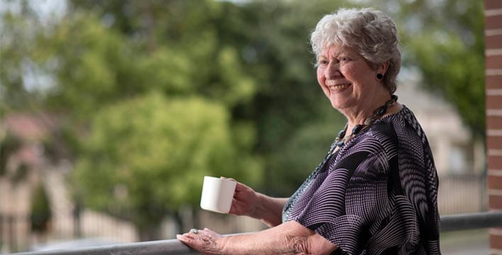 lady on balcony drinking a cup of tea - 'retirement villages near me' concept